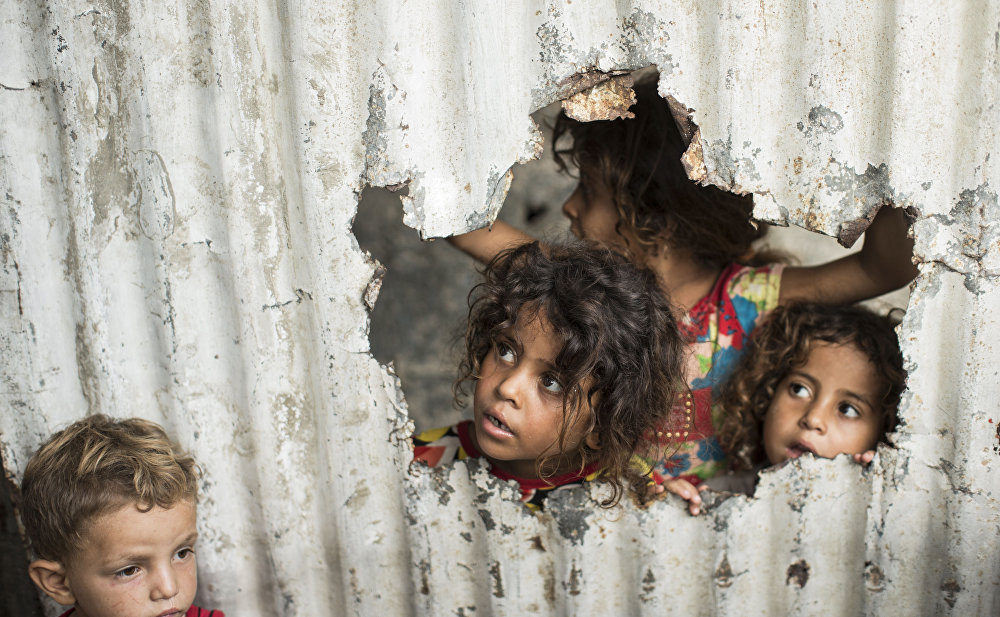 Palestinian children look through a hole in a sheet metal fence outside their home in a poor neighbourhood in Gaza City