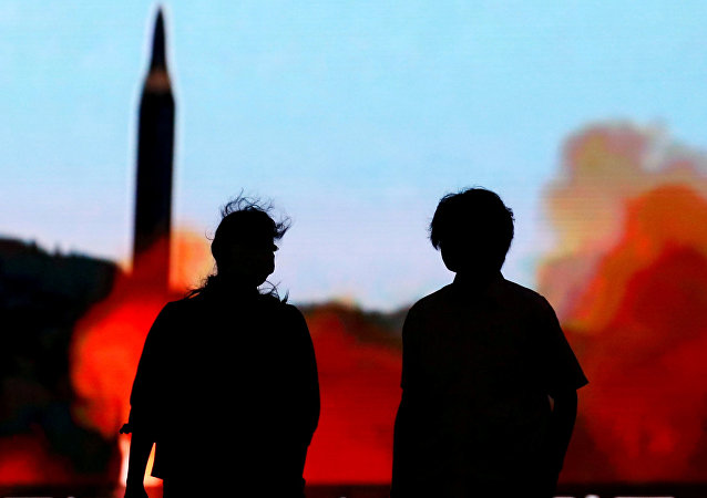 People walk in front of a monitor showing news of North Korea's fresh threat in Tokyo, Japan, August 10, 2017.