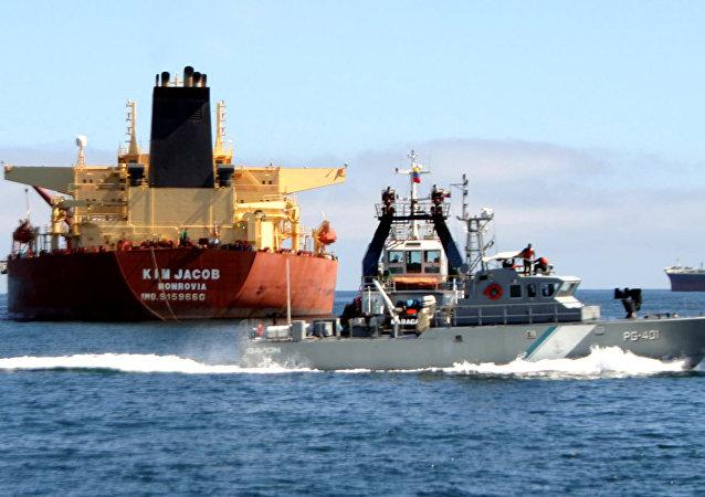 A Venezuelan patrol boat passes oil tanker Kim Jacob carrying 1 million barrels of crude that ran aground in Venezuelan waters near Borracha Island off Venezuela's eastern state of Anzoategui, Tuesday, Jan. 31, 2006
