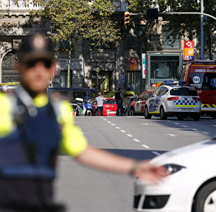 A policemen stand as he blocks the street to a cordoned off area after a van ploughed into the crowd, injuring several persons on the Rambla in Barcelona on August 17, 2017