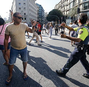 A policeman asks people to move back near a cordoned off area after a van ploughed into the crowd, killing one person and injuring several others on the Rambla in Barcelona on August 17, 2017