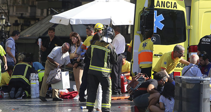 Injured people are treated in Barcelona, Spain, Thursday, Aug. 17, 2017 after a white van jumped the sidewalk in the historic Las Ramblas district, crashing into a summer crowd of residents and tourists and injuring several people, police said.