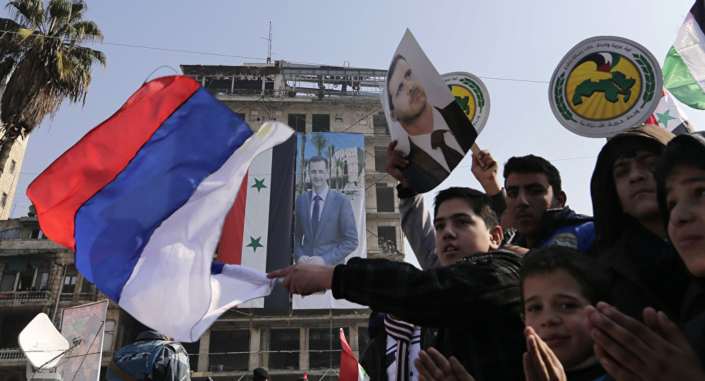 Pro-government supporters wave the Russian national flag and pictures of Syrian President Bashar Assad, as gathering at the Saadallah al-Jabiri Square in Aleppo, Syria, Thursday, Jan. 19, 2017