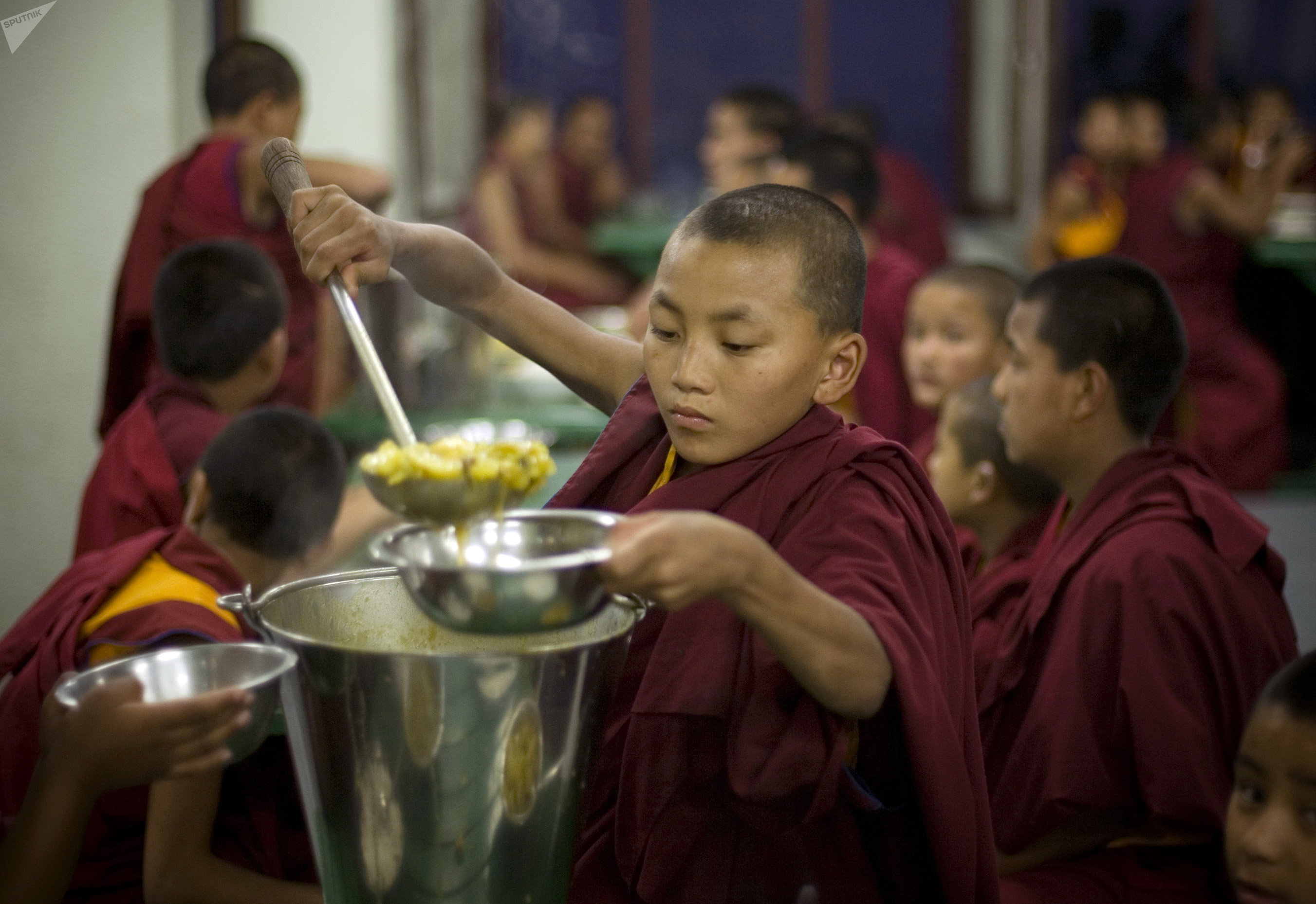 A young Buddhist monk serves food during dinner at the Kopan Monastery in Katmandu, Nepal. (File)