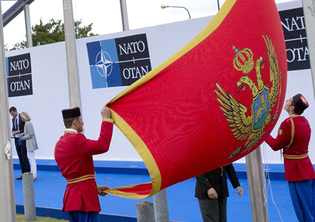 Soldiers from Montenegro unfurl the national flag during a ceremony to mark the accession of Montenegro at NATO Headquarters in Brussels on Wednesday, June 7, 2017