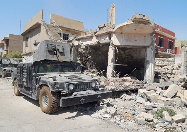 Iraqi army truck near house wreck in western Mosul, Iraq