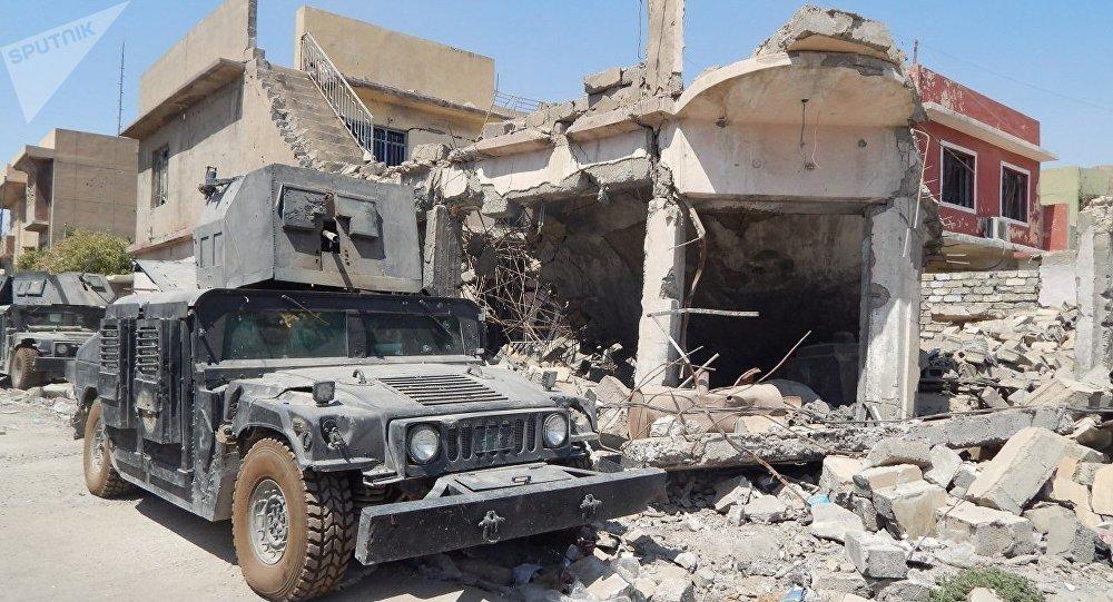Iraqi army truck near house wreck in western Mosul, Iraq