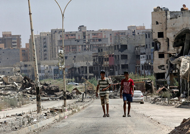 Men walk near destroyed buildings in Sabri, a central Benghazi district, Libya, August 12, 2017