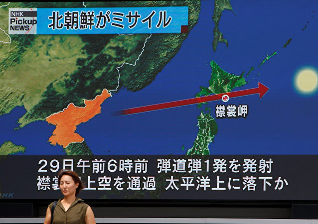 A woman walks past a large TV screen showing news about North Korea's missile launch in Tokyo, Japan, August 29, 2017.