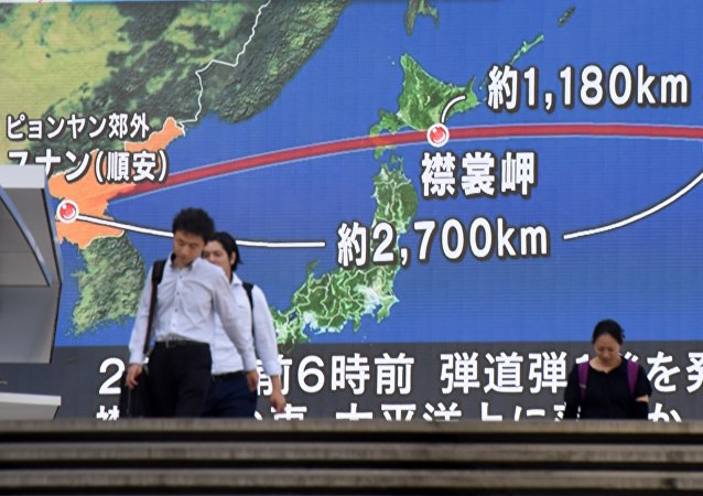 Pedestrians walk in front of a huge screen displaying a map of Japan (R) and the Korean Peninsula, in Tokyo on August 29, 2017, following a North Korean missile test that passed over Japan.