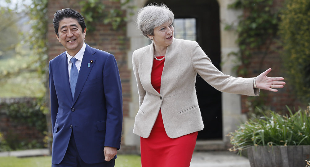 Britain's Prime Minister Theresa May shows Prime Minister Shinzo Abe of Japan around the garden at Chequers near Wendover, England, Friday, April 28, 2017.