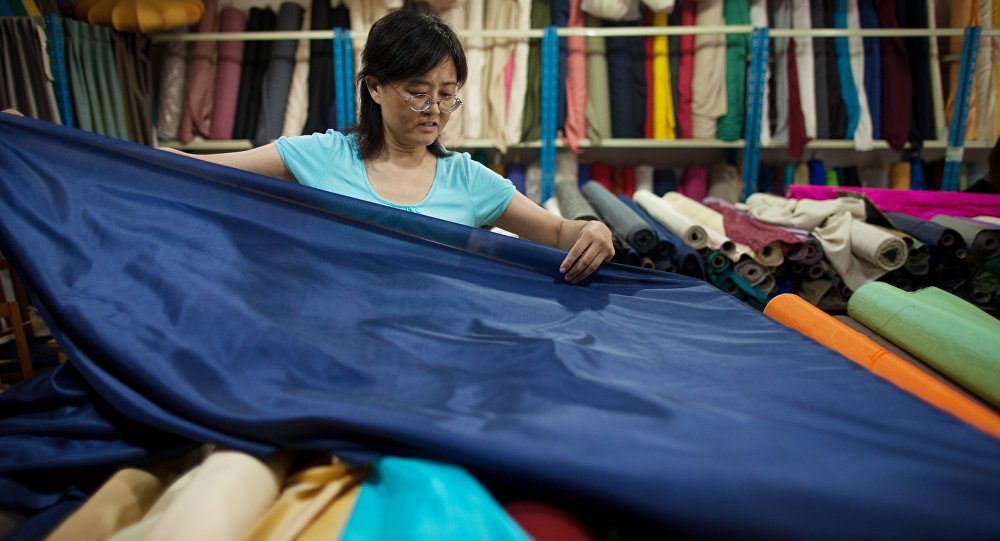 A vendor prepares rolls of silk at her textile and fabric shop in Beijing