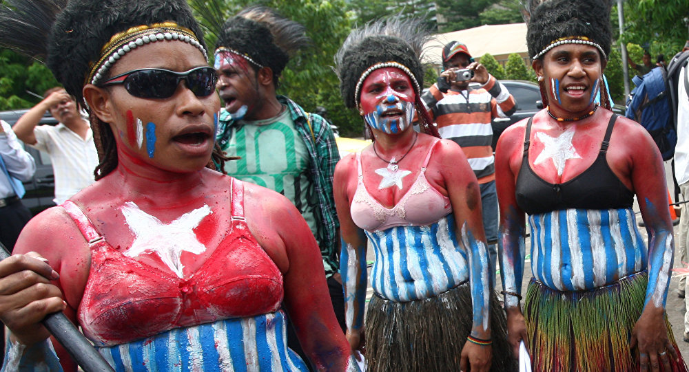 Papuan activists, their body painted with the colors of 'Morning Star' separatist flag, take part in a rally marking the 50th anniversary of failed efforts by Papuan tribal chiefs to declare independence from Dutch colonial rule in 1961, in Jakarta, Indonesia, Thursday, Dec. 1, 2011.