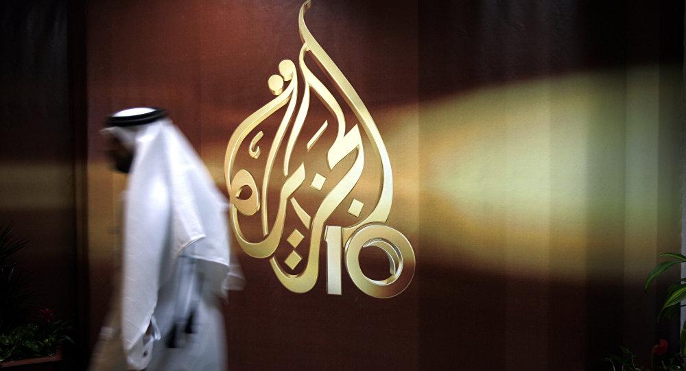 A Qatari employee of Al Jazeera Arabic language TV news channel passes by the logo of Al Jazeera in Doha, Qatar. (File)