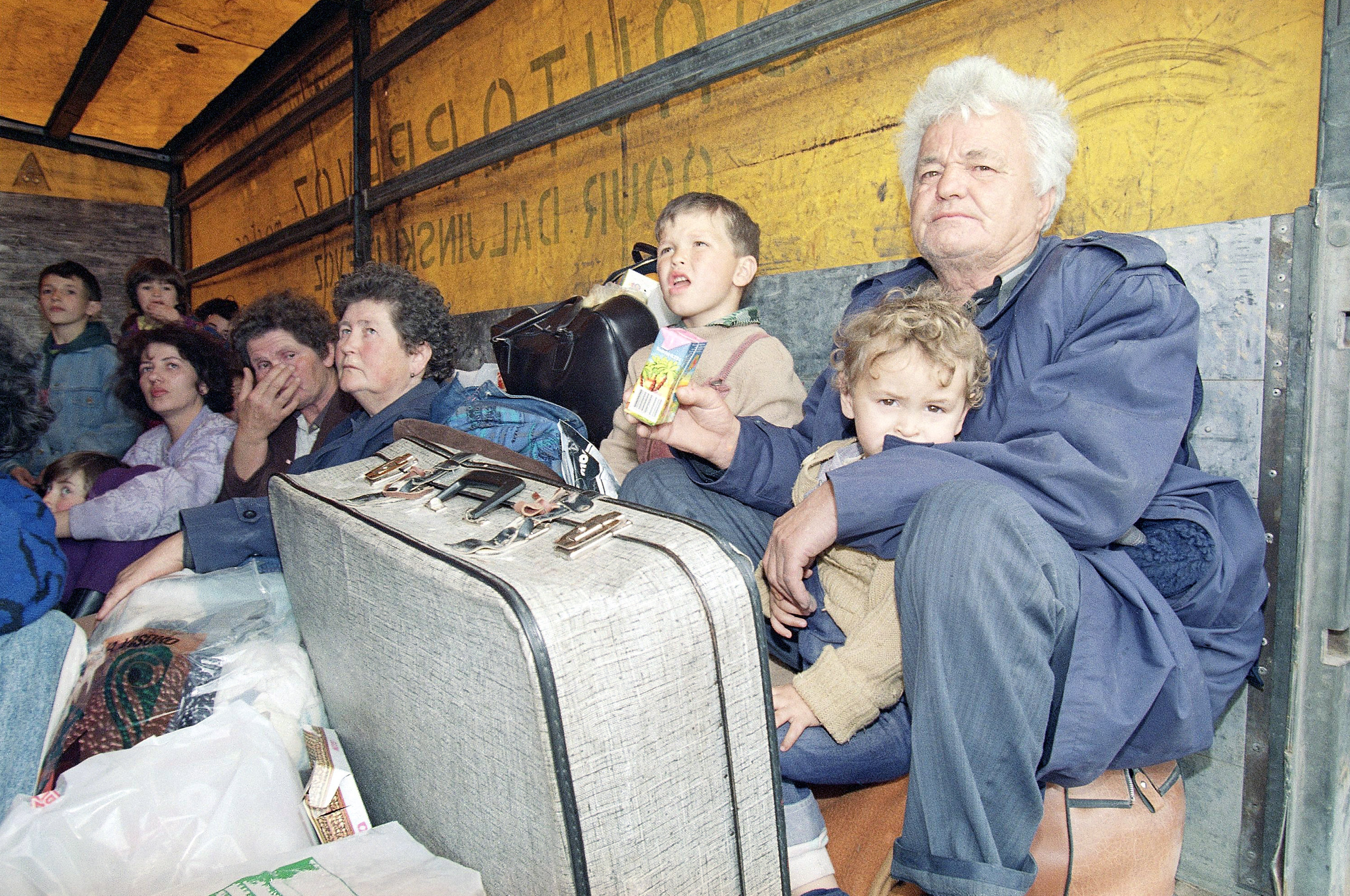 Bosnian refugees from Siroki Brijeg, on the frontline close to Mostar in Bosnia-Herzegovina, sit in a truck along with their belongings waiting to embark on a ferry to the island of Brace, in Split's harbor, Croatia on April 9, 1992.