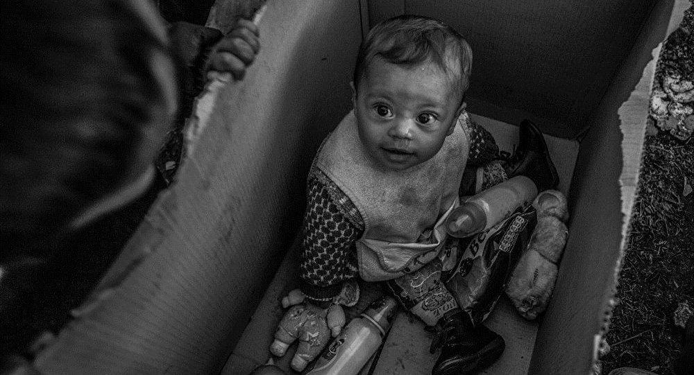A baby sits in a cardboard box in the Idomeni camp on the Greek-Macedonian border