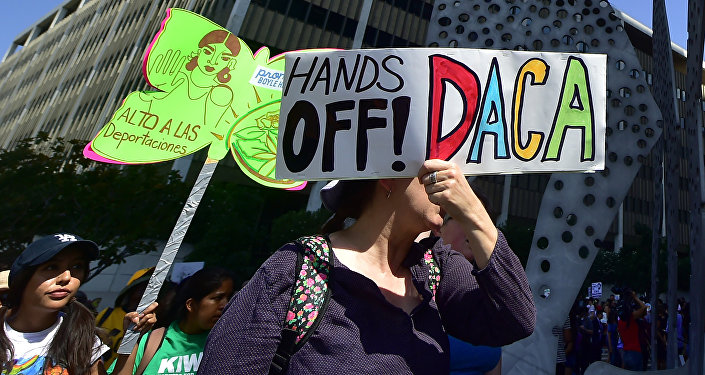 Young immigrants and supporters walk holding signs during a rally in support of Deferred Action for Childhood Arrivals (DACA) in Los Angeles, California