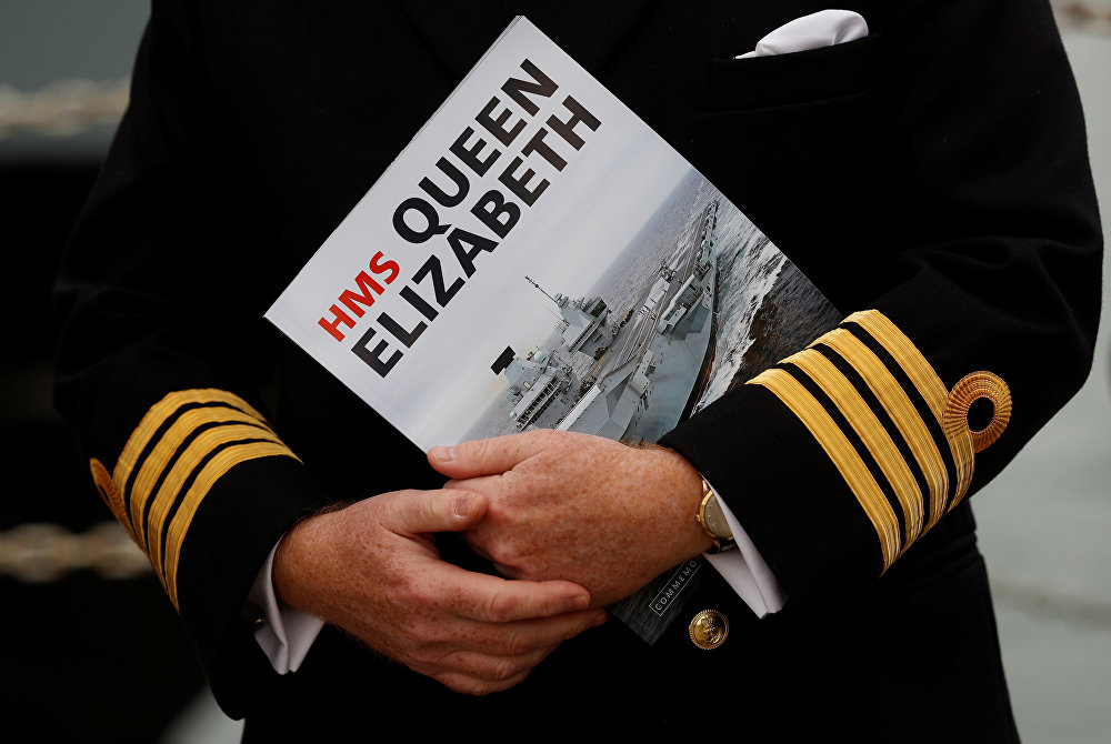 A Naval officer listens to speeches after the arrival of the Royal Navy's new aircraft carrier HMS Queen Elizabeth in Portsmouth, Britain August 16, 2017.