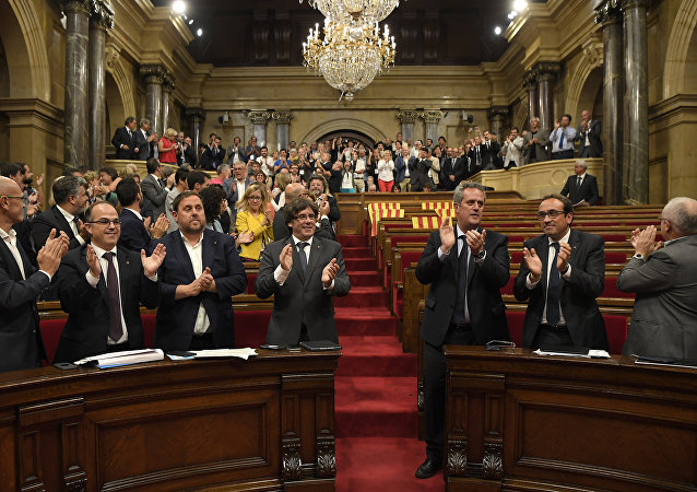 President of the Catalan Government Carles Puigdemont (4thL), Catalan regional vice-president and chief of Economy and Finance and leader of the Esquerra Republicana de Catalunya (ERC) leftist republican party Oriol Junqueras (3rdL) and other members of the Catalan Parliament applaud the results of the vote on a bill for a referendum on independence in Barcelona