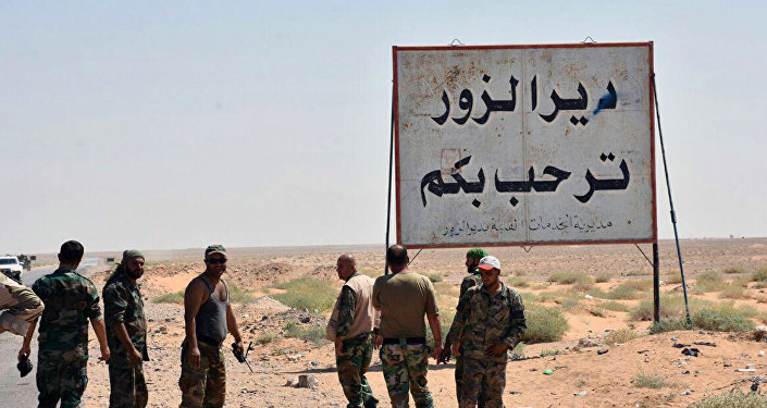 This photo released on Sunday, Sept 3, 2017 by the Syrian official news agency SANA, shows Syrian troops and pro-government gunmen standing next to a placard in Arabic which reads, Deir el-Zour welcomes you, in the eastern city of Deir el-Zour, Syria