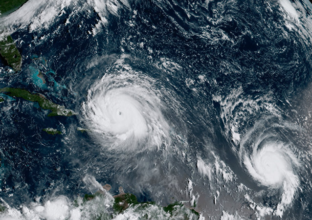 In this GOES-16 geocolor image satellite image taken Thursday, Sept. 7, 2017, the eye of Hurricane Irma, left, is just north of the island of Hispaniola, with Hurricane Jose, right, in the Atlantic Ocean