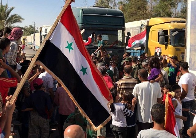 Deir ez-Zor residents welcome a truck convoy of medicines and food