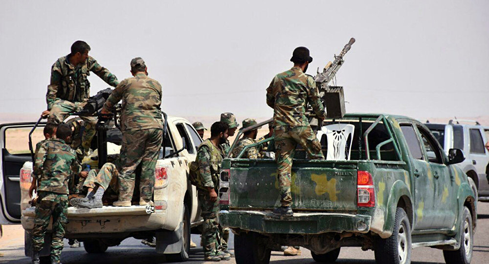 This photo released on Monday, Sept 4, 2017 by the Syrian official news agency SANA, shows Syrian troops and pro-government gunmen standing on pickup trucks with heavy machine-guns mounted on them, in the eastern city of Deir el-Zour, Syria