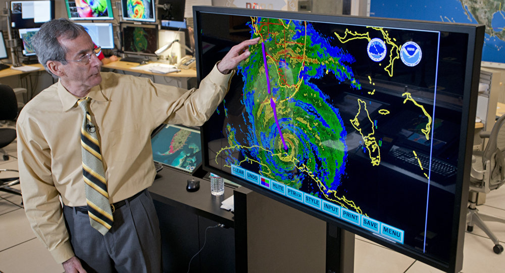 Ed Rappaport, the acting director of the National Hurricane Center, draws a line to illustrate the projected track of Hurricane Irma up Florida's west coast Saturday, Sept. 9, 2017 during a television interview