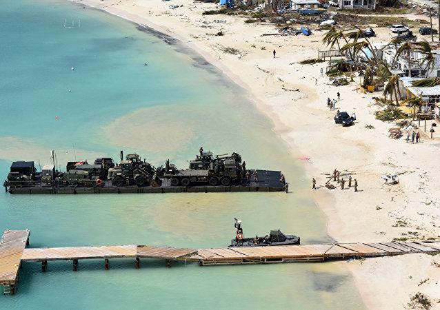 In this undated photo provided by the Ministry of Defence on Friday, Sept. 8, 2017, taken from a Royal Navy helicopter, a RLC Mexeflote approaches Sandy Bay Village beach, in Anguilla loaded with the 2 JCBs, 1 flatbed lorry, fork lift truck, BV 206 multi terrain vehicle, a Land Rover and a mobile generator.