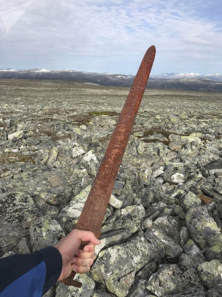 In this photo taken on Aug. 23, 2017, Einar Ambakk, one of the hunters that found an ancient Viking sword slid down between rocks during a reindeer hunt, raises it in Lesja, some 275 kilometers (170 miles) north of Oslo. According to a Norwegian archeologist, the nearly 1-meter-long (3-foot) sword dating from about 850-950 A.D. may have been left by a person who got lost in a blizzard and died on the mountain from exposure.