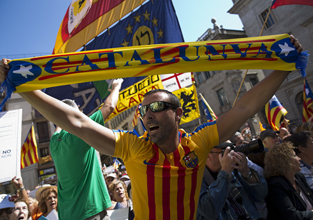 People wave esteladas or independence flags and banners in support of the mayors under investigation as they take part in a march, outside the Generalitat Palace, to protest against the ruling of the constitutional court ahead of a planned independence referendum in the Catalonia region, in Barcelona, Spain, Saturday, Sept. 16, 2017