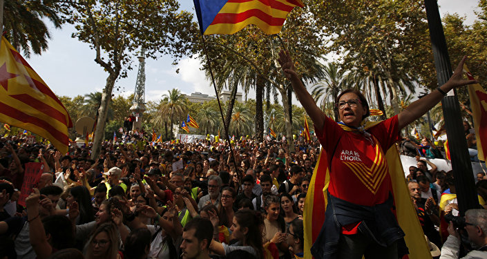 A woman gestures as others wave the estelada or Catalonia independence flags during a protest in Barcelona, Spain Thursday, Sept. 21, 2017.