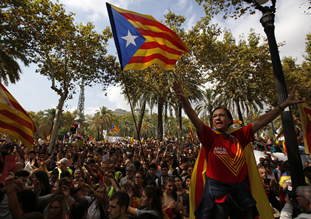 A woman gestures as others wave the ''estelada'' or Catalonia independence flags during a protest in Barcelona, Spain Thursday, Sept. 21, 2017