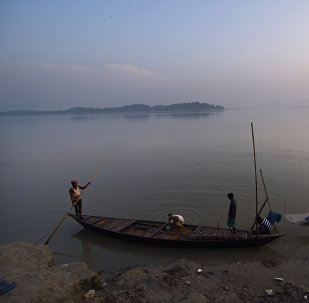 In this photograph taken on June 4, 2016, Indian boatman prepare to cast off after buying fish at a wholesale local fish market on the banks of the River Bhramaputra in Guwahati