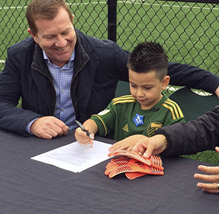 Five-year-old Derrick Tellez, center, signs his contract with Portland Timbers general manager Gavin Wilkinson, left, and coach Caleb Porter, right, on Friday, Sept. 22, 2017, at the Timbers' practice facility in Beaverton, Ore.