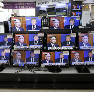 TV screens show a news program with an image of U.S. President Donald Trump and North Korean leader Kim Jong Un