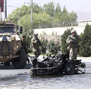 U.S. and Afghan security forces inspect the site of a suicide attack on NATO convoy in Kabul, Afghanistan, Sunday, Sept. 24, 2017