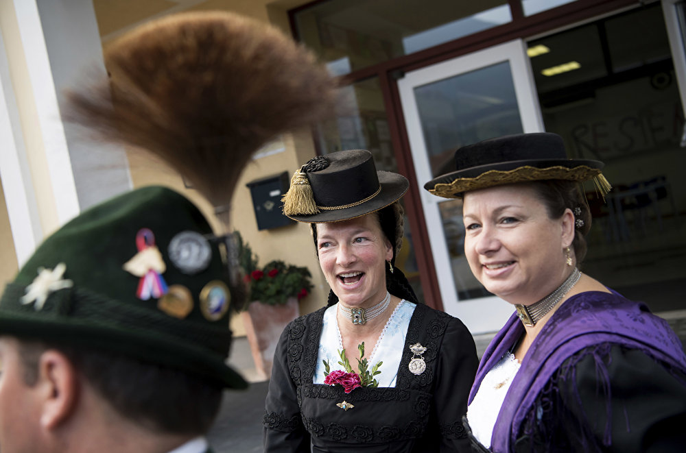 Women and a man in traditional Bavarian costumes stand at a polling station after casting their vote in the German parliament election in Unterwoessen, southern Germany, Sunday, Sept. 24, 2017