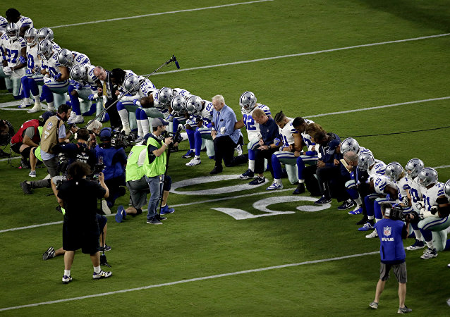 The Dallas Cowboys, led by owner Jerry Jones, center, take a knee prior to the national anthem prior to an NFL football game against the Arizona Cardinals, Monday, Sept. 25, 2017, in Glendale, Ariz.