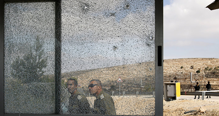 Members of the Israeli security forces walk past the shattered glass of the security post at the entrance to the West Bank settlement of Har Adar after a Palestinian opened fire on security personnel in a fatal attack before being shot dead