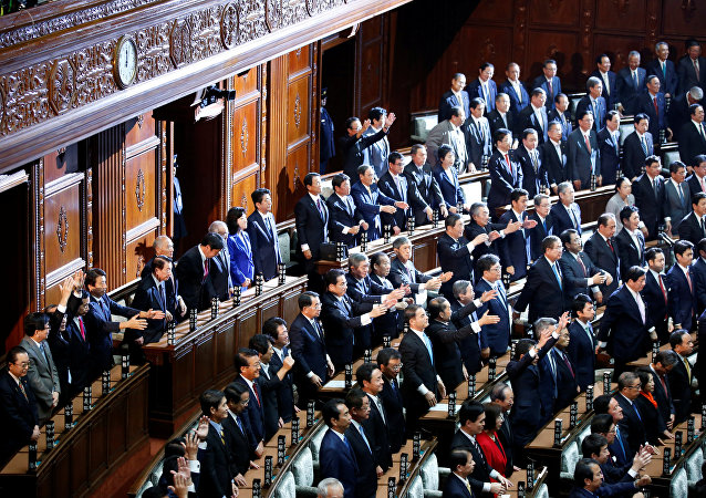 Lawmakers raise their hands and shouts banzai (cheers) after the dissolution of lower house was announced at the Parliament in Tokyo, Japan