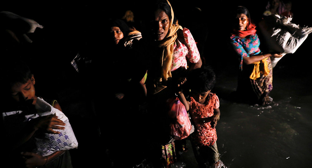 Women and children wade through the water as hundreds of Rohingya refugees arrive under the cover of darkness by wooden boats from Myanmar to the shore of Shah Porir Dwip, in Teknaf, near Cox's Bazar in Bangladesh, September 27, 2017