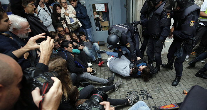 Spanish police officers immobilize some people outside a polling station in Barcelona, on October 1, 2017, on the day of a referendum on independence for Catalonia banned by Madrid