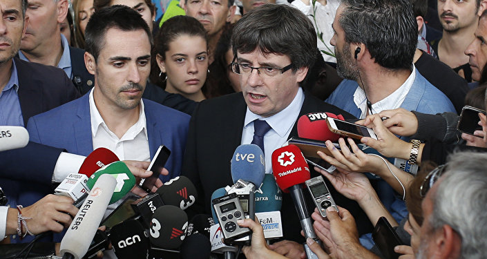 Catalan President Carles Puigdemont, centre, speaks to the media at a sports center, assigned to be a polling station by the Catalan government and where Puigdemont was originally expected to vote, in Sant Julia de Ramis, near Girona, Spain, Sunday, Oct. 1, 2017. Scuffles earlier erupted as voters protested as dozens of anti-rioting police broke into a polling station.