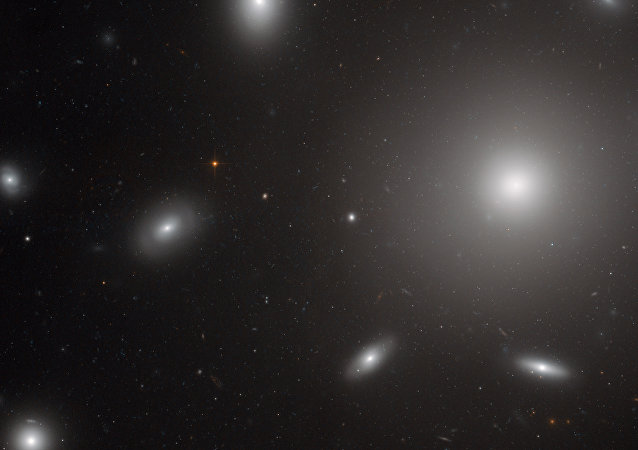 A photo of the center of the Coma Galaxy Cluster. The bright spherical shape is NGC 4874, a galaxy with an extremely powerful gravitational pull that is surrounded by globular clusters of stars.
