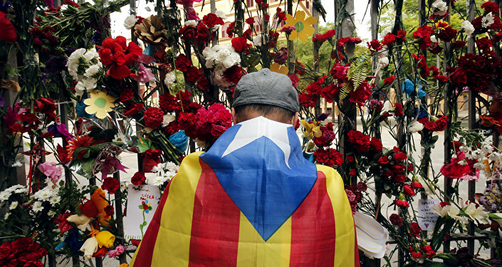 A man wrapped in a Catalan pro-independence 'Estelada' flag puts flowers on the gate of Barcelona's Ramon Llull School, which was used as a polling station and was one of those targeted by riot police during the October 1 banned independence referendum, as Catalonia observes a general strike called by Catalan unions on October 3, 2017