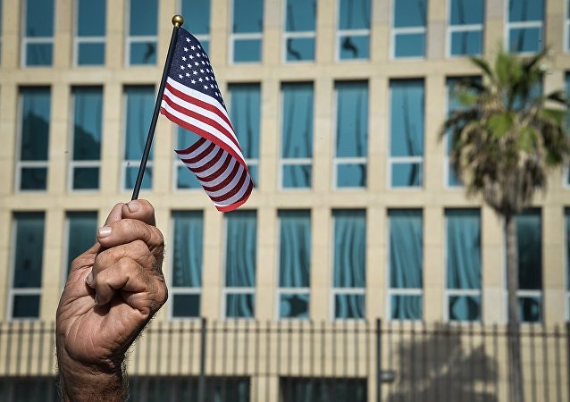 A Cuban holds a little US flag in front of the US Embassy in Havana. (File)