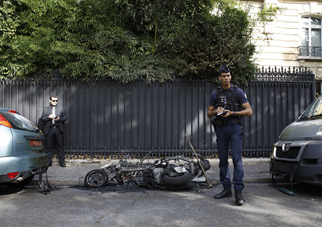 A police officer stands next to a burnt scooter outside the office of Jordan's military attache in Paris, Wednesday, Oct. 4, 2017