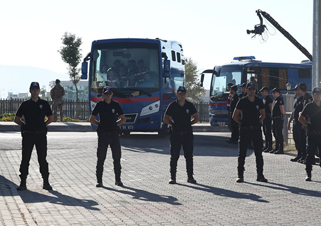 Riot police stand guard as prison vehicles, carrying soldiers accused of attempting to assassinate Turkish President Tayyip Erdogan on the night of the failed last year's July 15 coup arrive for a trial in Mugla, Turkey