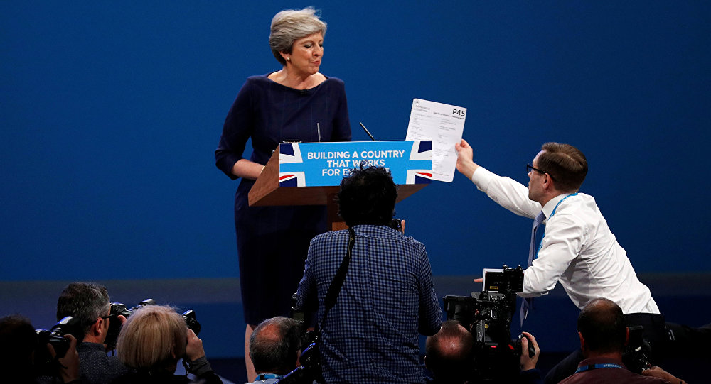 A member of the audience hands a P45 form (termination of employment tax form) to Britain's Prime Minister Theresa May as she addresses the Conservative Party conference in Manchester, October 4, 2017.